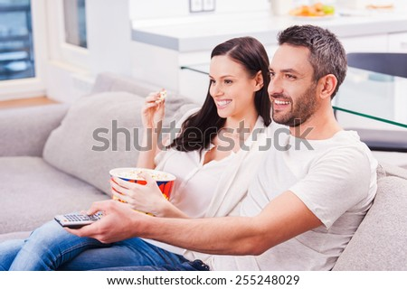 Enjoying their favorite show. Beautiful young loving couple bonding to each other and eating popcorn while sitting on the couch and watching TV  - stock photo