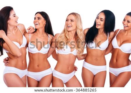 Enjoying their perfection. Group of five beautiful women in lingerie embracing and looking at each other with smiles while standing against white background - stock photo