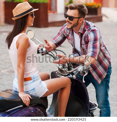Enjoying their time together. Beautiful young couple talking to each other and smiling while woman sitting on scooter - stock photo
