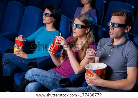 Enjoying three-dimensional movie. Top view of people in three-dimensional glasses watching movie while sitting at the cinema  - stock photo
