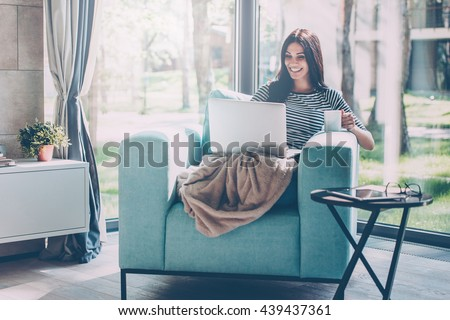 Enjoying time at home. Beautiful young smiling woman working on laptop and drinking coffee while sitting in a big comfortable chair at home