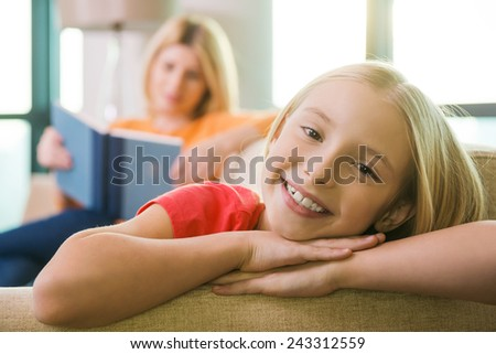 Enjoying time near mother. Happy little girl sitting on the couch and smiling while her mother reading book in the background - stock photo