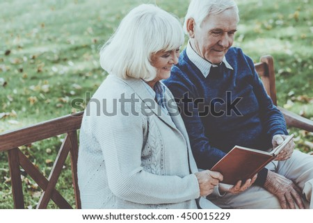 Enjoying time together. Cheerful senior couple reading a book together while sitting on the park bench - stock photo