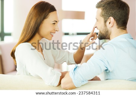 Enjoying time together. Playful young loving couple sitting together on the couch and looking at each other with smile while woman touching nose of her boyfriend - stock photo