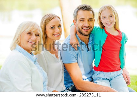 Enjoying time with family. Happy family bonding to each other and smiling while sitting outdoors together  - stock photo