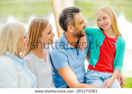 Enjoying time with family. Happy family communicating and smiling while sitting outdoors together  - stock photo