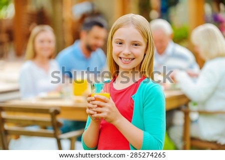 Enjoying time with family. Happy little girl holding glass with orange juice and smiling while her family sitting at the dining table in the background  - stock photo