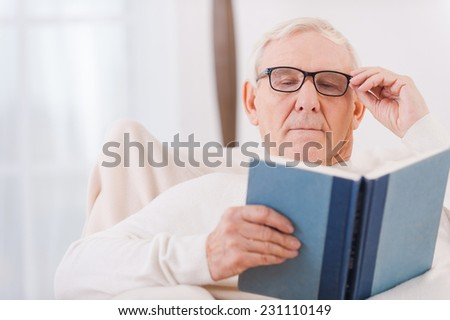 Enjoying time with favorite book. White hair senior man reading a book while sitting in chair at his apartment  - stock photo