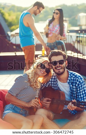 Enjoying time with friends. Beautiful young couple bonding to each other and sitting on the bean bag with guitar while two people barbecuing in the background  - stock photo