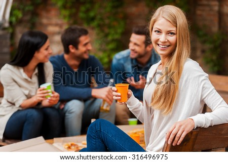 Enjoying time with friends. Smiling young woman holding glass and looking at camera while her friends talking to each other in the background   - stock photo