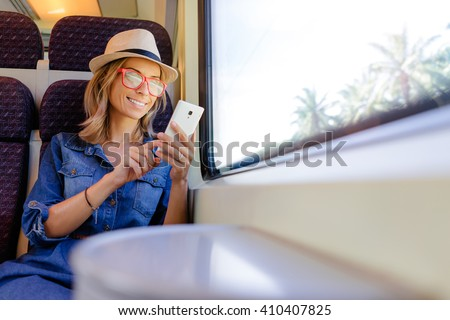 Enjoying travel. Young pretty woman traveling by the train sitting near the window using smartphone. - stock photo