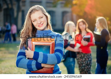 Enjoying university life. Pretty young woman with long hair holding books and smiling while standing against university with her friends chatting in the background out of focus - stock photo