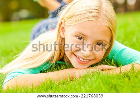 Enjoying warm summer day. Cute little girl looking at camera and smiling while lying on the green grass  - stock photo