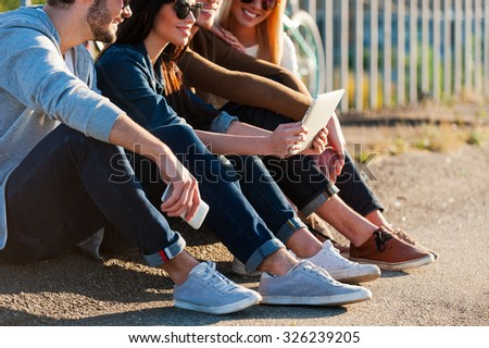 Enjoying wireless technologies. Close-up of group of young smiling people bonding to each other and looking at digital tablet while sitting outdoors together - stock photo