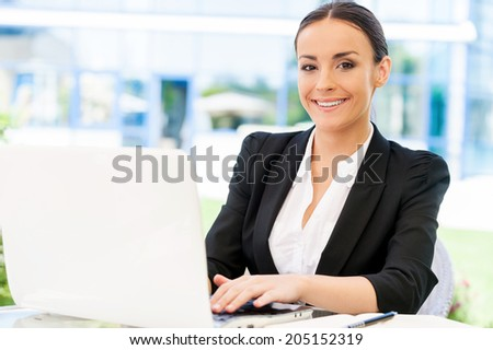 Enjoying working outdoors. Attractive young businesswoman in formalwear working on laptop and smiling while sitting at the table outdoors - stock photo
