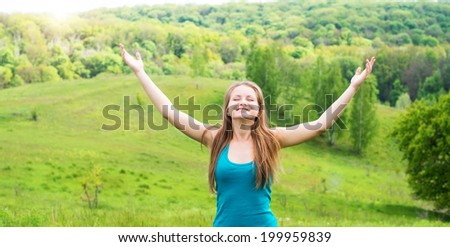 Enjoyment - free happy woman enjoying nature. Girl with arms outspread and face raised in sky enjoying peace, serenity in nature. Happy woman relaxing outdoors with arms open. - stock photo