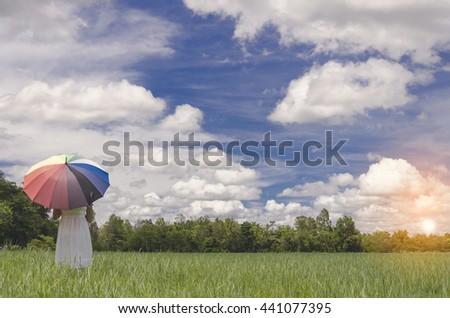 Enjoyment - free happy woman enjoying sunrise. Beautiful woman in white dress with  holding umbrella in blue sky enjoying peace, serenity - stock photo