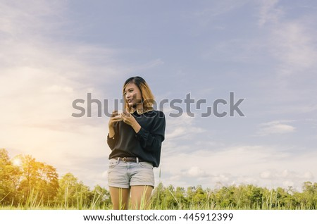 Enjoyment - free happy woman enjoying sunrise. smile young woman holding cup of coffee or tea on on on the meadow and sunrise  - stock photo