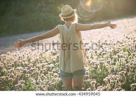 Enjoyment - free happy woman enjoying sunset. Beautiful woman embracing the golden sunshine glow of sunset with arms outspread enjoying peace, serenity in nature - stock photo