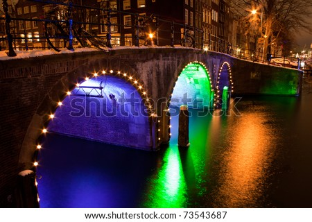 Enlightened bridge over canal in Amsterdam by night - stock photo