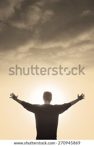 enlightened man with faith praying under god light - stock photo