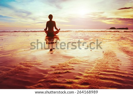 enlightenment, silhouette of woman practicing yoga on the beach - stock photo