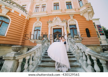 Enloved wedding couple at stairs of romantic antique palace. Groom holding beautiful bride on his hands