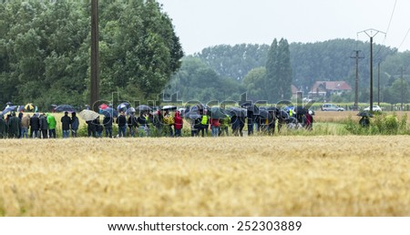 ENNEVELIN, FRANCE - JUL 09: Cycling fans waiting for the peloton in North of France on the cobble-stoned roads from Ennevelin during the stage 5 of Le Tour de France in Ennevelin on July 09 2014.