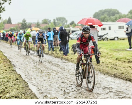 ENNEVELIN, FRANCE - JUL 09:The Columbian cyclist John Darwin Atapuma (BMC Team) riding on a cobbled road during the stage 5 of Le Tour de France in Ennevelin on July 09 2014. . - stock photo