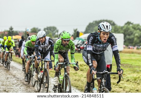 ENNEVELIN, FRANCE - JUL 09:The peloton riding on a cobbled road during the stage 5 of Le Tour de France in Ennevelin on July 09 2014.