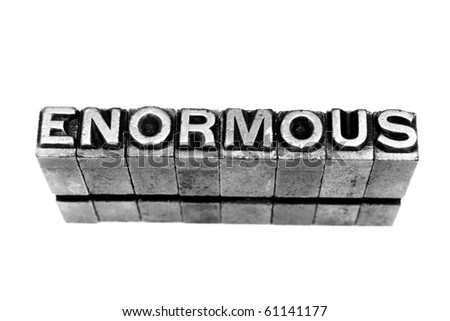 ENORMOUS written in metallic letters on a white background - stock photo