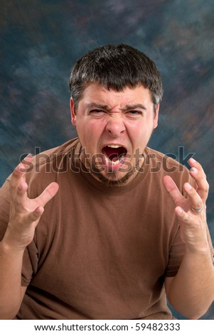 Enraged man who is close to tears, screams and gestures with his hands. - stock photo