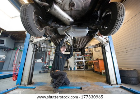 ENSCHEDE, NETHERLANDS - DEC 13: A mechanic is checking the exhaust of a car who is lifted up in a repair service station, December 13, 2013 in the Netherlands - stock photo