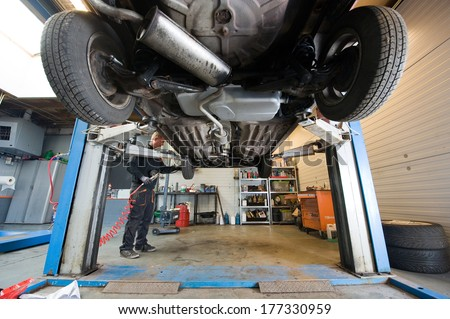 ENSCHEDE, NETHERLANDS - DEC 13: A mechanic is working on the wheel of a car who is lifted up in a repair service station, December 13, 2013 in the Netherlands - stock photo
