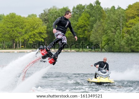 ENSCHEDE, NETHERLANDS - MAY 12: A man is giving a show how to keep in balance, and shows what you can do with the new sensation called flyboarding, May 12, 2013 in the Netherlands. - stock photo