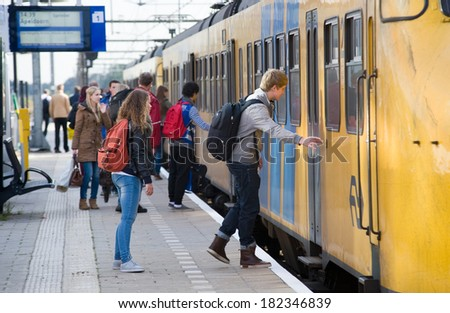 ENSCHEDE, NETHERLANDS: People are stepping into a train that just arrived on a railway platform of a small station, oct 18, 2012 in the Netherlands - stock photo