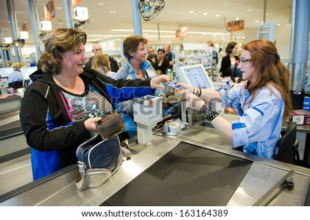 ENSCHEDE, THE NETHERLANDS - JUNE 27: A woman is paying the products that she has choosen in the Albert Heijn supermarket, at a female cashier with a creditcard,  June 27, 2013 in the Netherlands. - stock photo