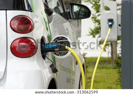 ENSCHEDE, THE NETHERLANDS - JUNE 02, 2015: An electric car is parked at a parking spot and is being recharged at a power station. - stock photo