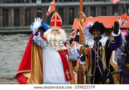 ENSCHEDE, THE NETHERLANDS - NOV 14, 2015: The dutch Santa Claus called 'Sinterklaas' is arriving with his helper Black Pete on a steamboat in a harbor in Holland.