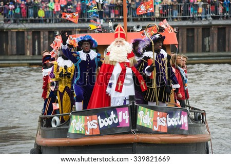 ENSCHEDE, THE NETHERLANDS - NOV 14, 2015: The dutch Santa Claus called 'Sinterklaas' is arriving with his helpers Black Pete on a steamboat in a harbor in Holland.