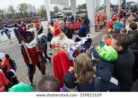 ENSCHEDE, THE NETHERLANDS - NOV 14, 2015: The dutch Santa Claus called 'Sinterklaas' is greeting the children after he has arrived on a boat in a dutch harbor - stock photo