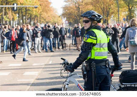 ENSCHEDE, THE NETHERLANDS - OCT 31, 2015: People are demonstrating against a huge migrant refugee camp for syrians close to the part of the city where they live. A police woman is watching them. - stock photo