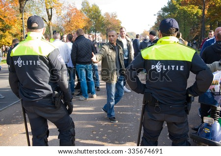 ENSCHEDE, THE NETHERLANDS - OCT 31, 2015: People are demonstrating against a migrant refugee camp for syrians close to where they live. Police men are stopping them, discussion follows.
