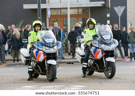 ENSCHEDE, THE NETHERLANDS - OCT 31, 2015: Two policemen on motorcycles on the street are watching the traffic. - stock photo