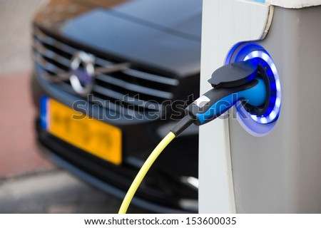 ENSCHEDE, The NETHERLANDS - SEPT 08: An electric car is parked at a parking spot in the center of a town while he is being recharged at a power station, September 08, 2013 in the Netherlands. - stock photo