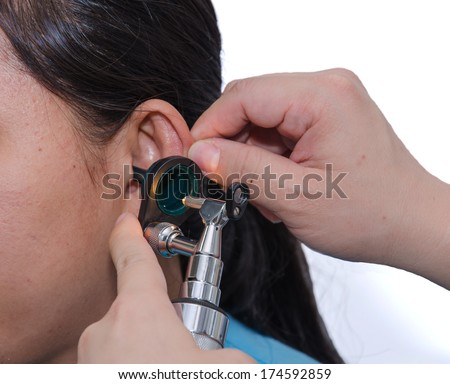 ENT physician checking patient's ear using otoscope with an instrument. - stock photo