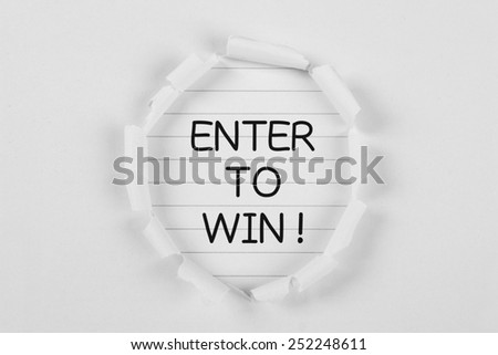 Enter to win on note paper with white tear paper. - stock photo