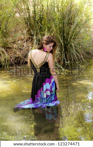 Entering a river dressed girl - stock photo