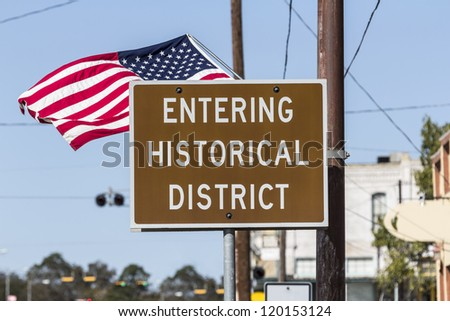 Entering historical district road sign with American Flag.