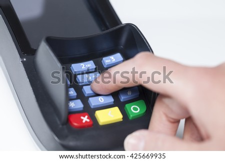 Entering Pin Code in a reading device for payment in a shop - stock photo